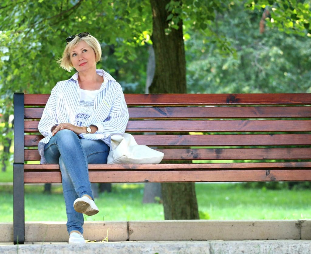 adult woman who looks younger than her age is sitting on a bench enjoying the beauty of the nature