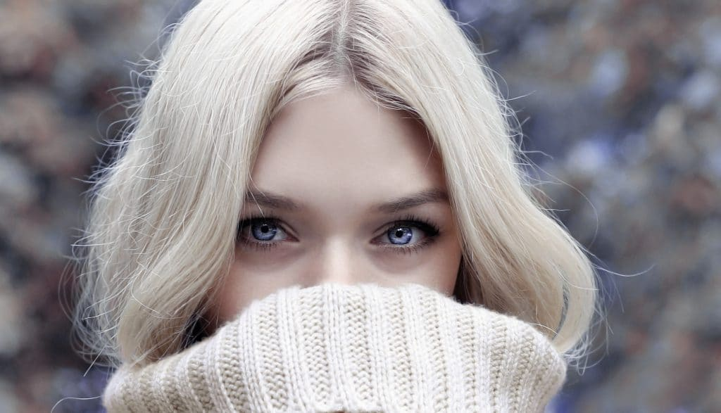 beautiful young woman covering her mouth with her sweater